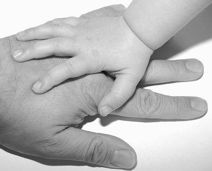 Mano di bimbo su mano del genitore