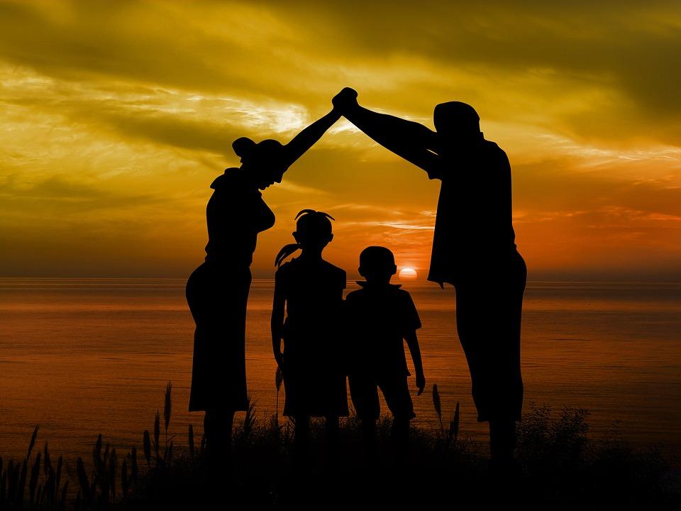 genitori che formano un tetto sui figli con le braccia